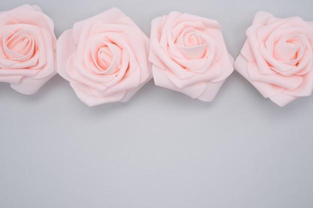 Nahaufnahmeaufnahme einer reihe von rosa rosen lokalisiert auf einem lila hintergrund mit kopienraum
