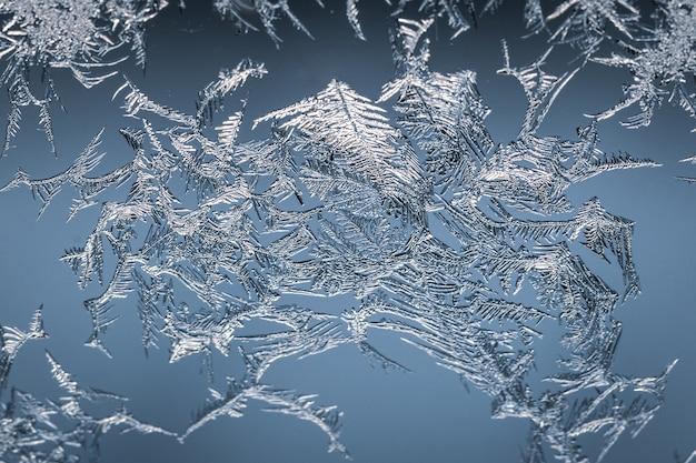 Nahaufnahmeaufnahme einer schneeflocke auf einem glas vom frost, mit detailliertem muster