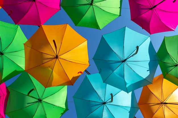 Nahaufnahmeaufnahme einer schönen anzeige des bunten hängenden regenschirms gegen einen blauen himmel