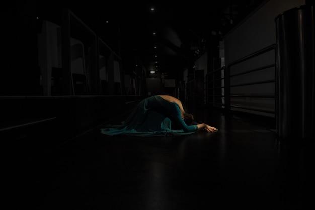 Nahaufnahmeaufnahme einer schönen ballerina, die eine ballettbewegung in einem dunklen bereich tut