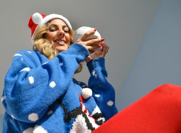 Nahaufnahmeaufnahme einer schönen jungen dame, die ein weihnachtskleid und einen hut hält eine weihnachtsmannschale hält