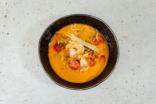 Nahaufnahmeaufnahme einer schüssel der köstlichen tom yum suppe auf einem weißen tisch