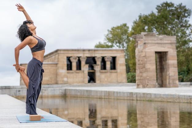 Nahaufnahmeaufnahme einer spanischen frau praktiziert yoga im freien