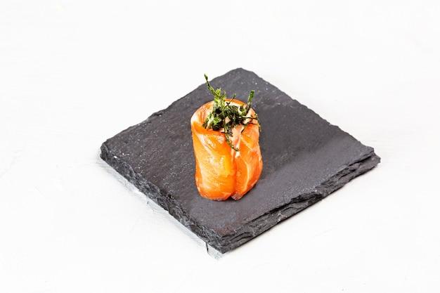 Nahaufnahmeaufnahme einer sushirolle auf einer schwarzen steinplatte