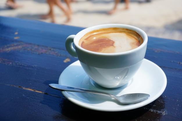 Nahaufnahmeaufnahme einer tasse kaffee auf einer weißen untertasse mit einem metalllöffel