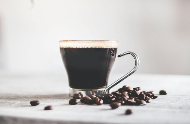 Nahaufnahmeaufnahme einer tasse schwarzen kaffees auf dem tisch mit gerösteten bohnen unter den lichtern