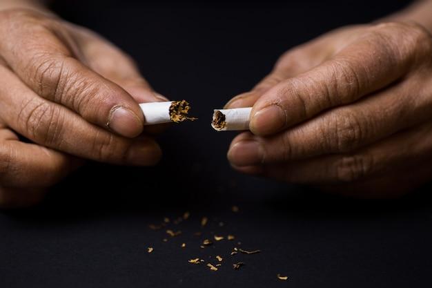 Nahaufnahmeaufnahme einer zigarette, die in halbem raucherentwöhnungskonzept geschnitten wird