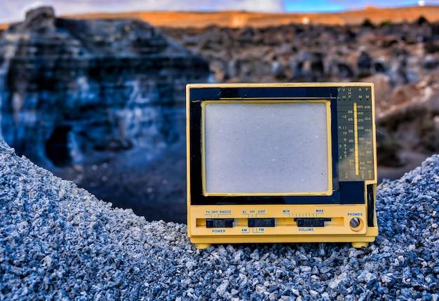 Nahaufnahmeaufnahme eines alten weinleseradiofernsehers auf einem felsen auf einem unscharfen hintergrund