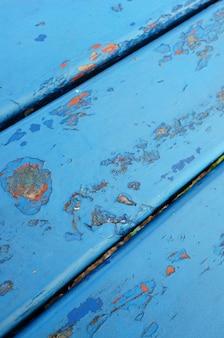 Nahaufnahmeaufnahme eines blauen metalltisches mit abgebrochener farbe, die alte schicht zeigt