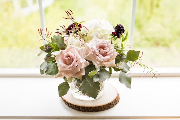 Nahaufnahmeaufnahme eines blumenstraußes mit rosen in einer vase nahe einem fenster unter dem sonnenlicht
