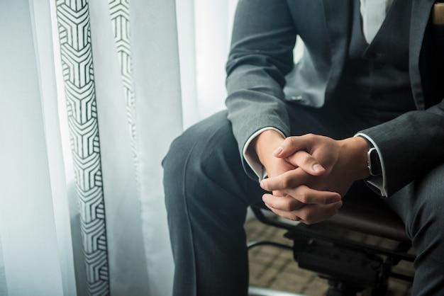Nahaufnahmeaufnahme eines bräutigams, der am fenster vor der hochzeitszeremonie sitzt