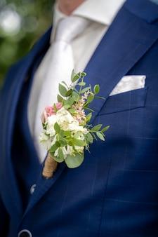 Nahaufnahmeaufnahme eines bräutigams mit einem blauen anzug zum zeitpunkt einer hochzeit