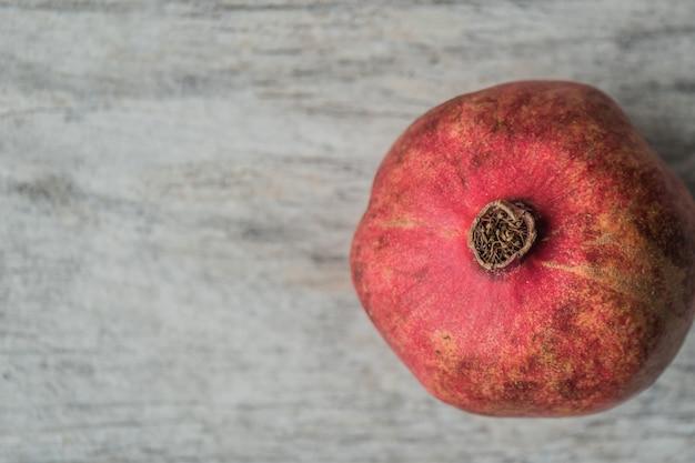 Nahaufnahmeaufnahme eines frischen reifen granatapfels auf einem grauen hintergrund
