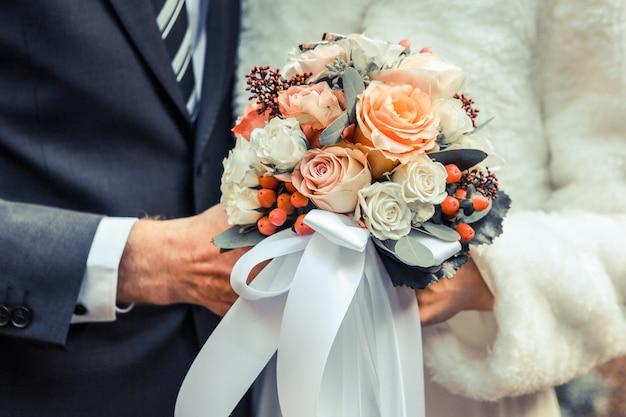 Nahaufnahmeaufnahme eines hochzeitspaares, das einen blumenstrauß mit weißen und orange rosen hält