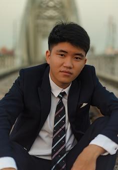 Nahaufnahmeaufnahme eines jungen asiatischen mannes in einem anzug, der in der mitte einer eisenbahnbrücke sitzt