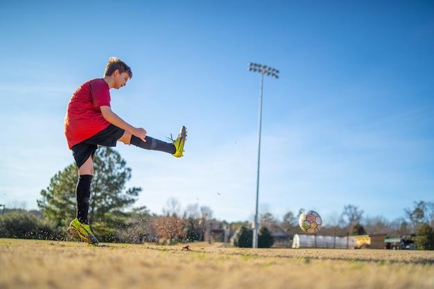 Nahaufnahmeaufnahme eines jungen, der fußball auf dem feld in einer roten uniform spielt