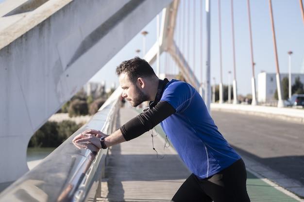 Nahaufnahmeaufnahme eines jungen mannes, der sich beim joggen an den rand der brücke stützt