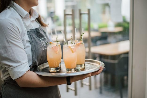 Nahaufnahmeaufnahme eines kellners, der cocktail mit frischen orangen auf einem silbernen tablett dient