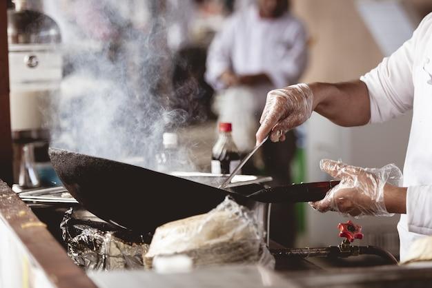 Nahaufnahmeaufnahme eines kochs, der mit einem unscharfen hintergrund kocht