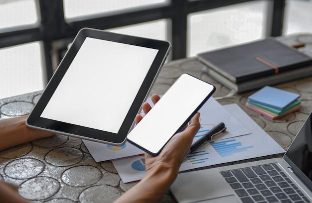 Nahaufnahmeaufnahme eines leeren bildschirmtabletts und des smartphones in der frauenhand und in einem laptop auf dem schreibtisch.