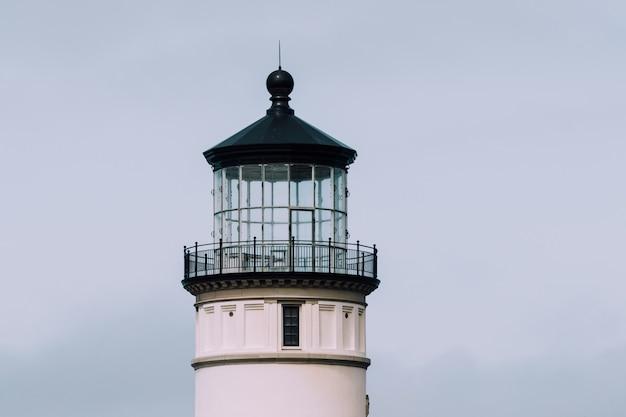 Nahaufnahmeaufnahme eines leuchtturms mit einem blauen bewölkten himmel