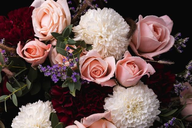 Nahaufnahmeaufnahme eines luxuriösen blumenstraußes der rosa rosen und der weißen blumen auf einem schwarzen hintergrund