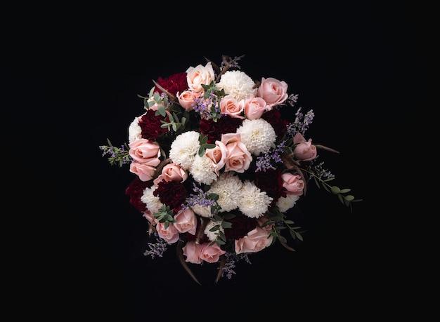 Nahaufnahmeaufnahme eines luxuriösen blumenstraußes von rosa rosen und weißen, roten dahlien auf einem schwarzen hintergrund