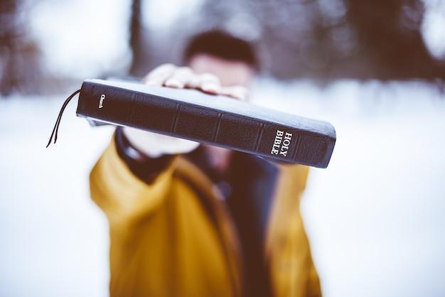 Nahaufnahmeaufnahme eines mannes, der die bibel in richtung hält