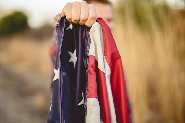 Nahaufnahmeaufnahme eines mannes, der die flagge der vereinigten staaten hält