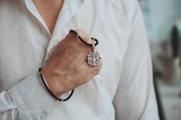 Nahaufnahmeaufnahme eines mannes, der eine charm-halskette mit einem silbernen anhänger und einer schwarzen schnur hält