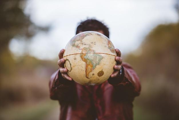 Nahaufnahmeaufnahme eines mannes, der eine lederjacke trägt, die einen globus vor ihm hält