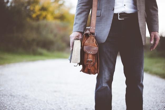 Nahaufnahmeaufnahme eines mannes, der einen geschäftsanzug trägt und steht, während er die bibel hält