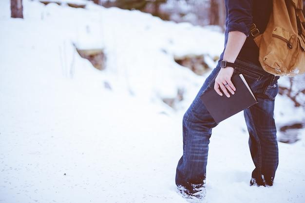 Nahaufnahmeaufnahme eines mannes, der einen rucksack trägt, der im schnee steht und die bibel hält