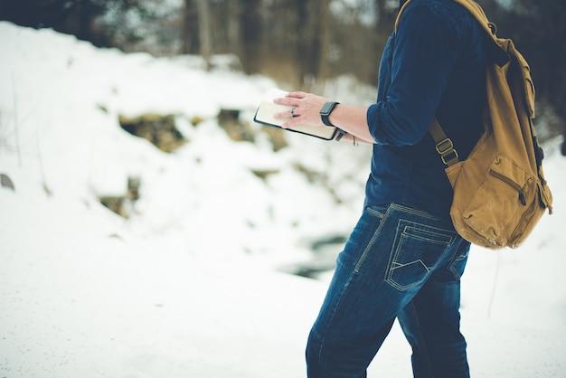 Nahaufnahmeaufnahme eines mannes, der einen rucksack trägt und die bibel liest