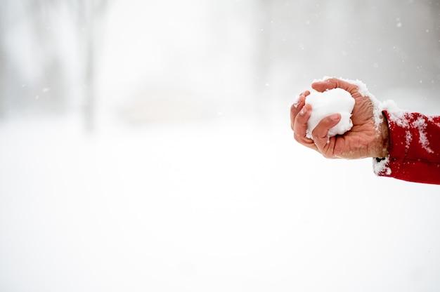 Nahaufnahmeaufnahme eines mannes, der einen schneeball hält