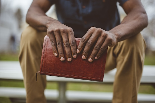 Nahaufnahmeaufnahme eines mannes, der im park sitzt, während die bibel hält