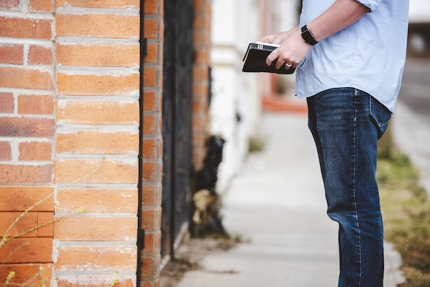 Nahaufnahmeaufnahme eines mannes, der nahe einem gebäude steht, während die bibel hält