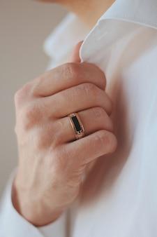 Nahaufnahmeaufnahme eines mannes in einem formellen outfit, das einen goldenen ring trägt