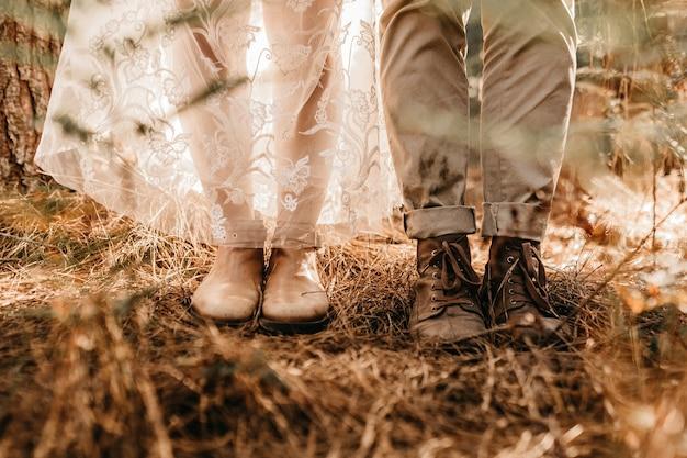 Nahaufnahmeaufnahme eines paares in alten stiefeln in einem feld mit getrocknetem gras während des tages