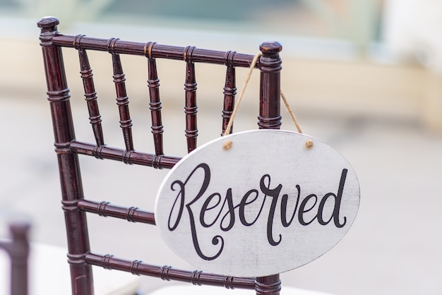 Nahaufnahmeaufnahme eines reservierten zeichens, das an einem stuhl bei einer hochzeitszeremonie hängt