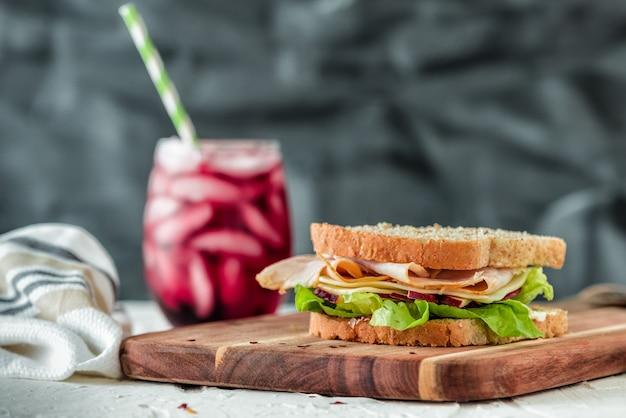 Nahaufnahmeaufnahme eines sandwiches auf einem hölzernen nahrungsmitteltablett mit einem gesunden fruchtshake