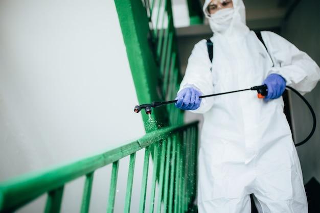 Nahaufnahmeaufnahme eines sanitären professionellen arbeiters, der schutzanzug desinfiziert, der einen treppenhaus-eingangsblock von wohnungen desinfiziert. coronavirus-prävention in wohnbereichen. neue normal- und stopp-covid-19-ausbreitung.
