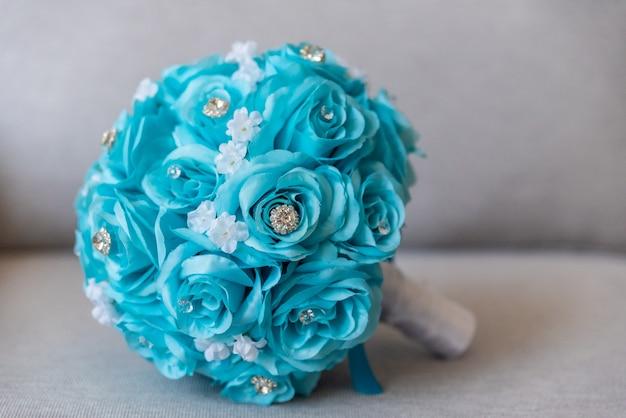 Nahaufnahmeaufnahme eines schönen hochzeitsstraußes, der von den blauen blumen und von den juwelen gemacht wird