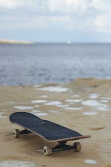 Nahaufnahmeaufnahme eines schwarzen skateboards auf dem nassen sand