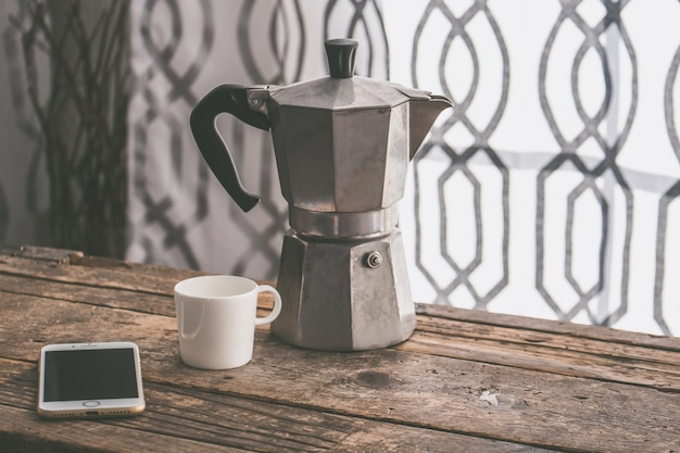 Nahaufnahmeaufnahme eines smartphones mit einem weißen becher und einer grauen teekanne auf einer holzoberfläche