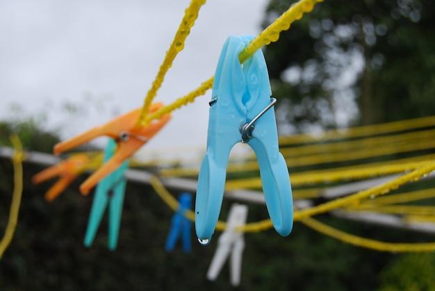 Nahaufnahmeaufnahme vieler bunter wäscheklammern auf gelben kabeln