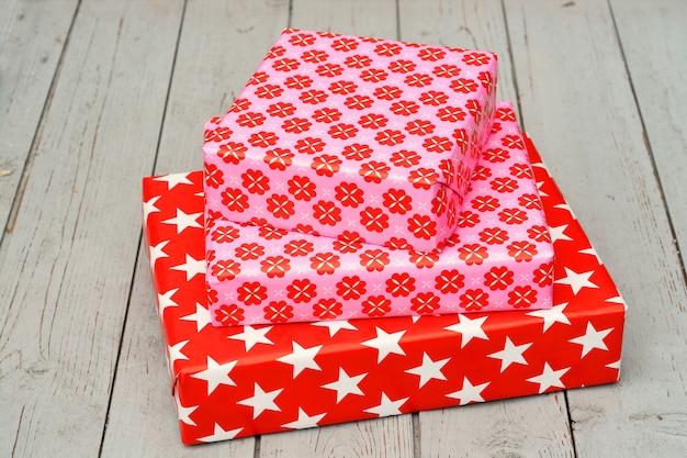 Nahaufnahmeaufnahme von drei geschenkboxen, die auf einer holzoberfläche übereinander gestapelt sind