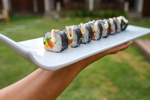 Nahaufnahmeaufnahme von jemandem, der ein tablett mit verschiedenen arten von sushi hält