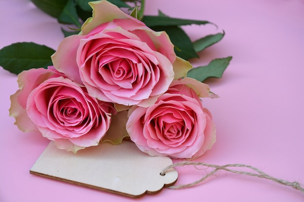 Nahaufnahmeaufnahme von rosa rosenblumen und einem etikett mit platz für text auf einer rosa oberfläche