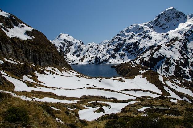 Nahaufnahmeaufnahme von schneebedeckten bergen und einem see von der routeburn-spur, neuseeland